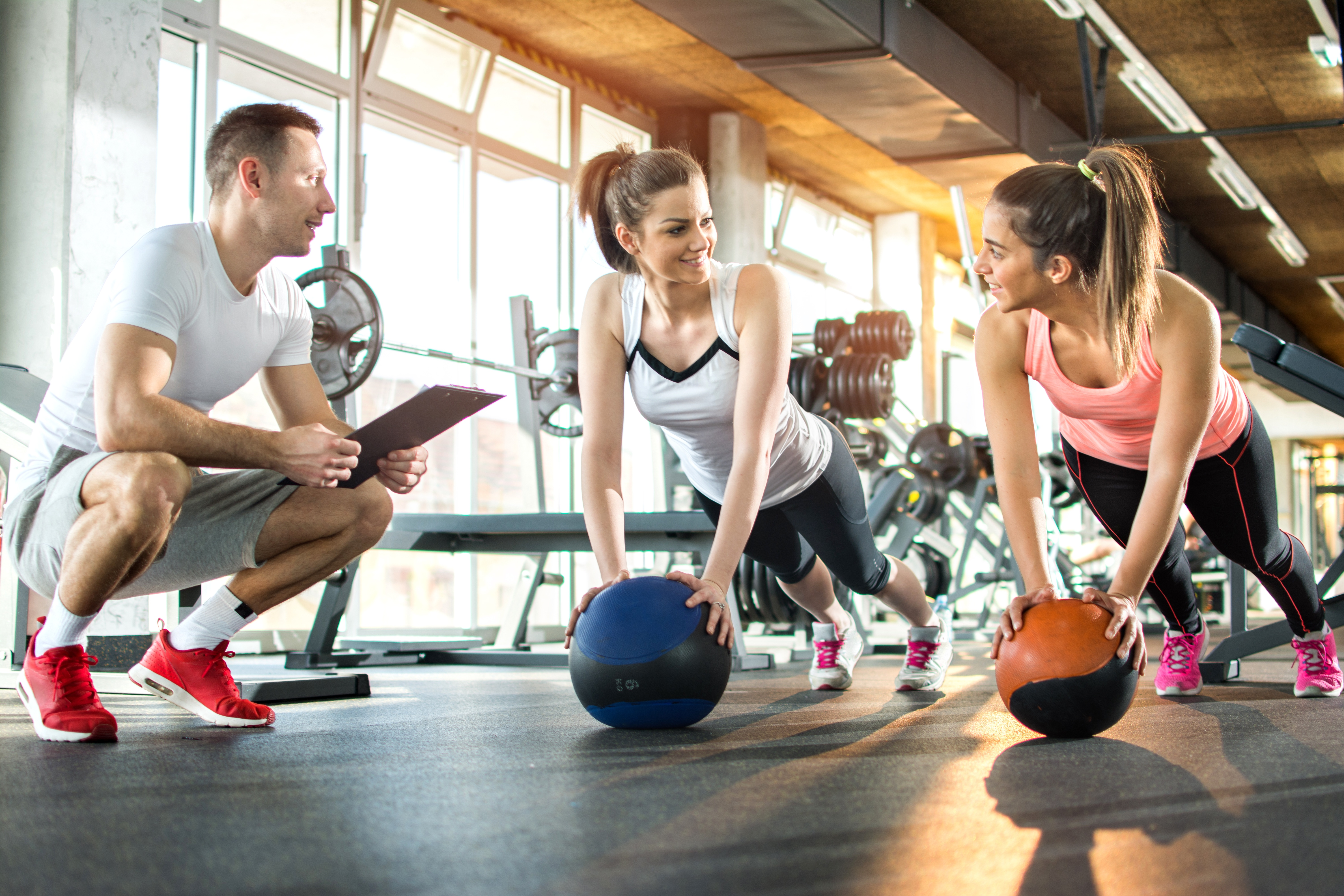 Two-sporty-girls-exercising-with-fitness-balls-while-their-fitness-instructor-tracking-the-progress-on-clipboard.-834605130_6000x4000